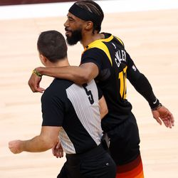 Utah Jazz guard Mike Conley (10) puts his arm around referee Kane Fitzgerald (5) as they walk back up court as the Utah Jazz and Memphis Grizzlies play Game 2 of their NBA playoffs first round series at Vivint Arena in Salt Lake City on Wednesday, May 26, 2021.