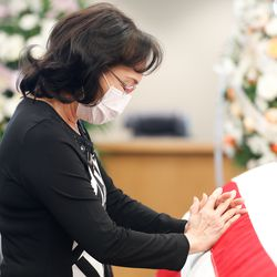 Fan Kwan pauses in front of the coffin to pay her last respects to Judge Michael Kwan at Taylorsville City Hall in Taylorsville on Friday, July 31, 2020. Kwan died July 21.