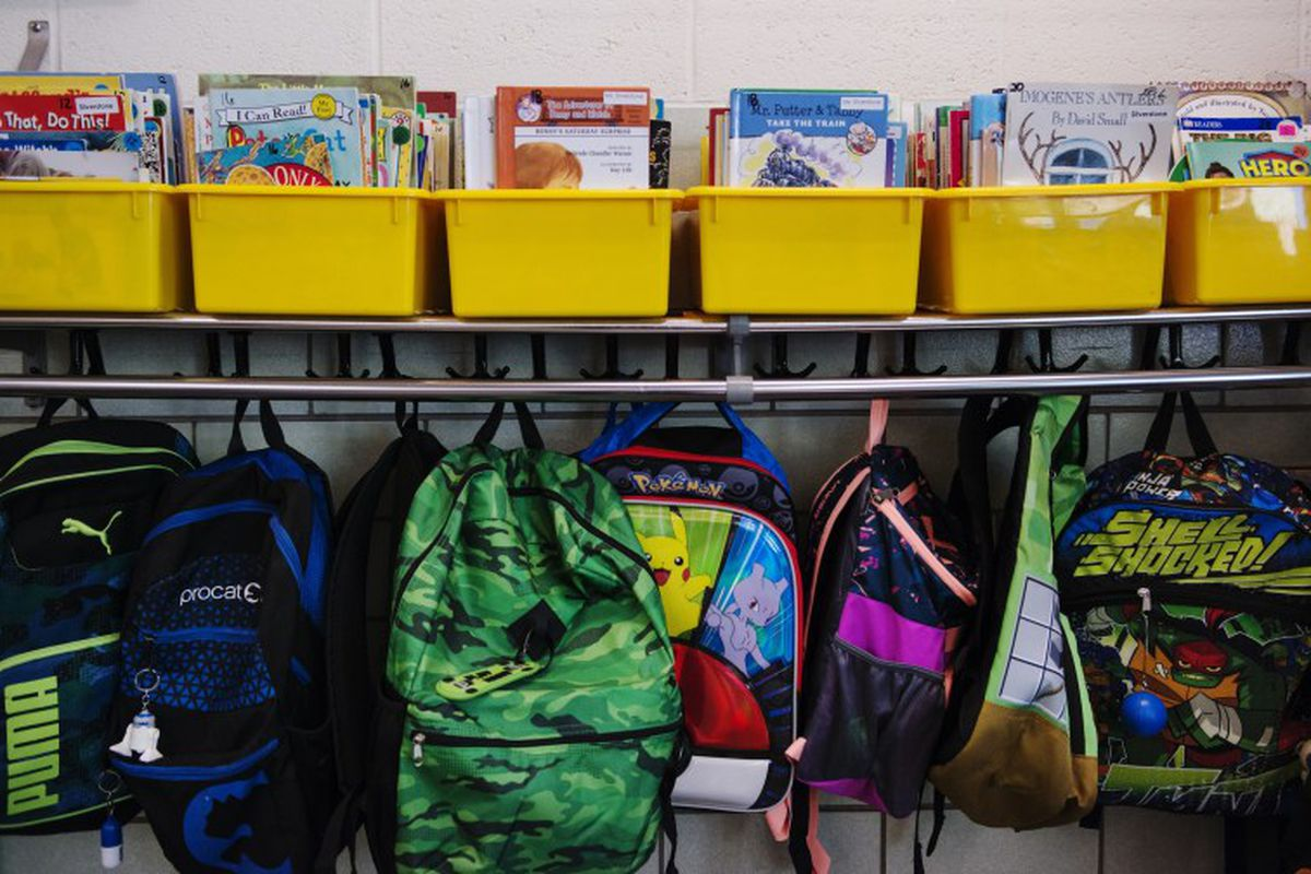 Backpacks hang from hooks in a classroom.