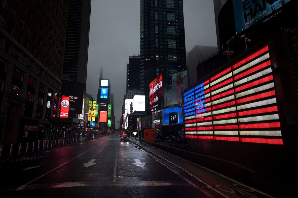 A US flag in lights on a wall in Times Square, New York, in front of an empty street at dusk.