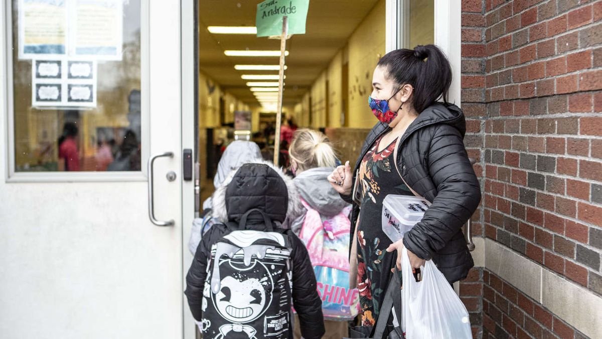 Students walk into school in Grand Rapids past a masked teacher holding the door