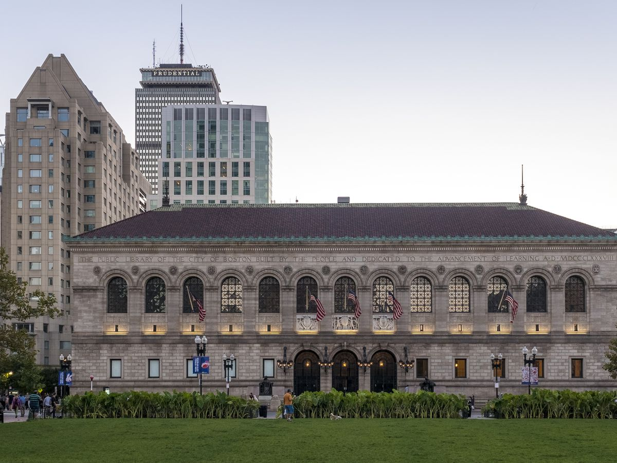 The exterior of the McKim building at the Boston Public Library. The building is large with many windows. There is a green lawn in front of the building.