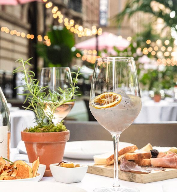 A clear cocktail with ice in a wine glass sits on an outdoor table with a rosemary plant, topped with a floating dried orange slice