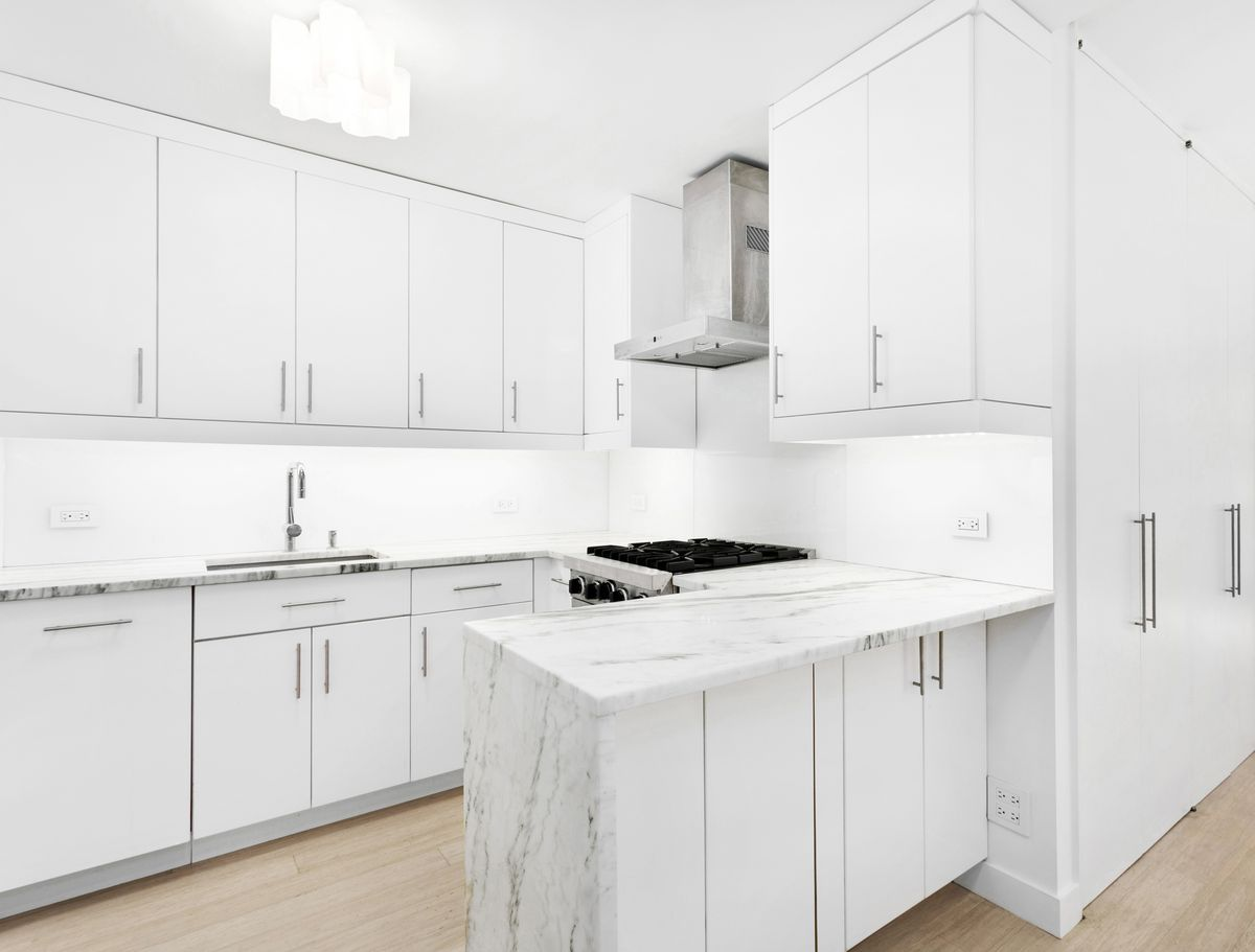 A kitchen with white cabinetry, marble countertops, and hardwood floors.