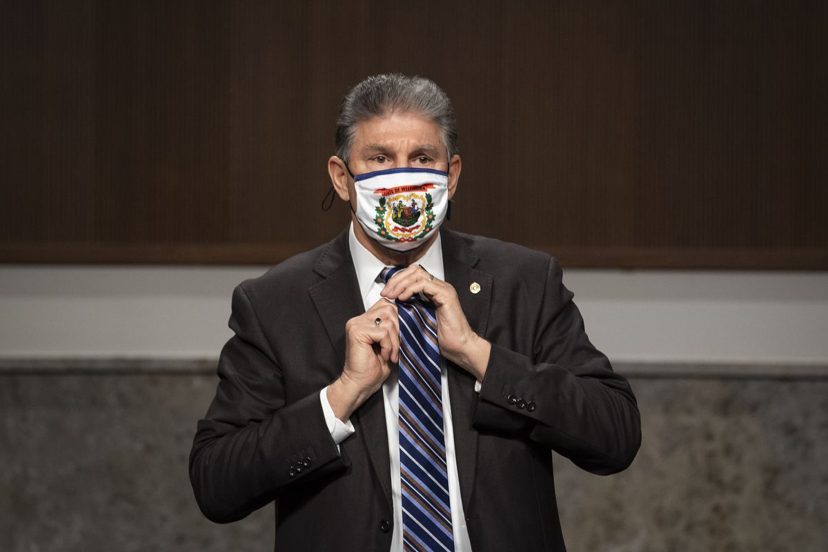 Manchin, in a dark suit, white shirt, and West Virginia flag mask, adjusts his blue and gray striped tie.