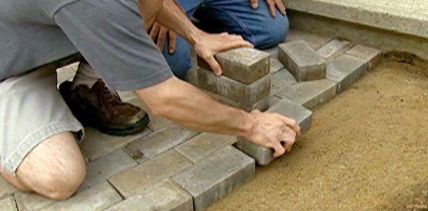 People laying bricks to build a paver walkway.