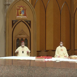 Cardinal Blase Cupich and Fr. Bill Vollmer listen to a reading and observe social distancing by sitting six feet apart during Holy Thursday Mass on Thursday, April 9, 2020 at Holy Name Cathedral