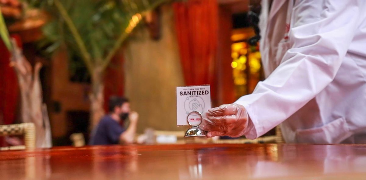 gloved hand placing sign that says sanitized on restaurant table