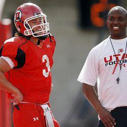 Utah Quarterback #3 Jordan Wynn, left, has a laugh with Offensive Coordinator/Quarterbacks Brian Johnson as Utah practices at Rice Eccles Stadium Tuesday, April 10, 2012.