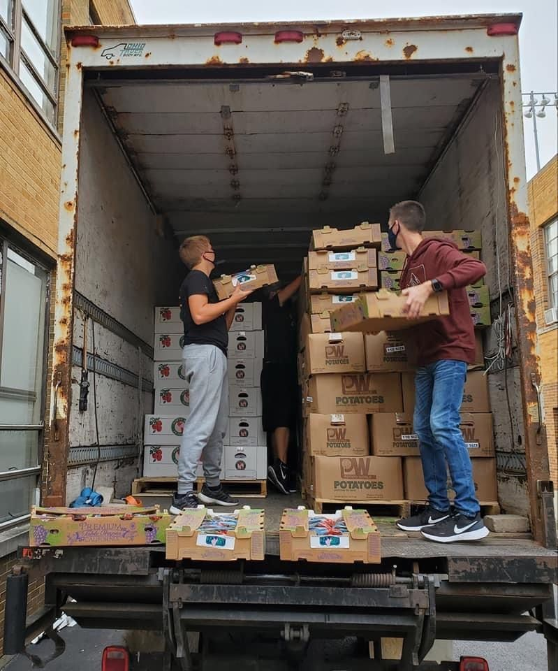 Students participating in JEE Foods unload food supplies from the back of a truck.