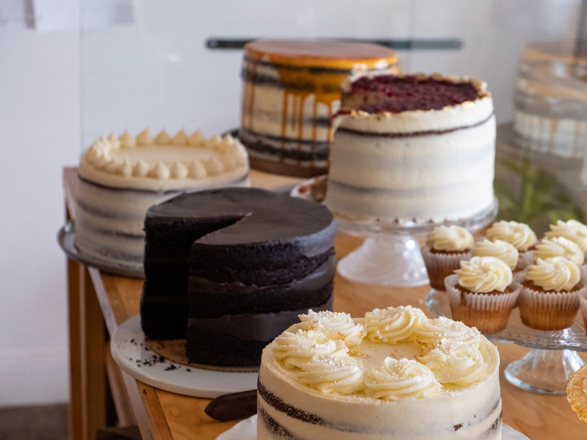 A collection of cakes, from chocolate to caramel, and some cupcakes to the right.