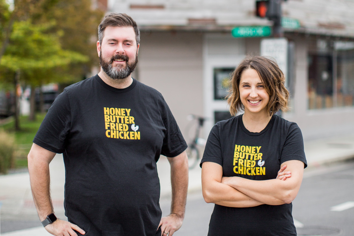 A man and woman wearing the same black T-shirts with the Honey Butter Fried Chicken logo standing outside and smiling.
