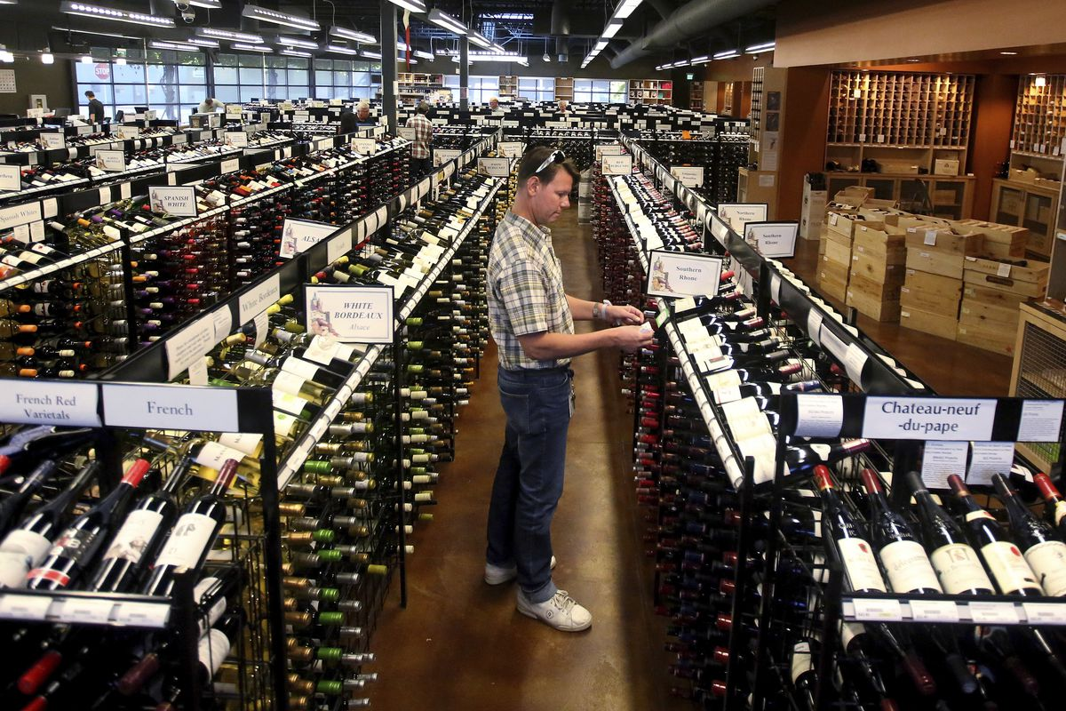 In this June 30, 2017, file photo, a worker at a state liquor store changes prices on wine, liquor and beer in Salt Lake City.