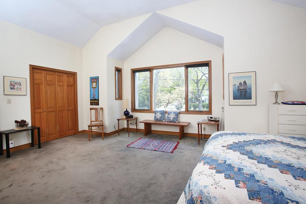 A bedroom with a high ceiling and a bed, and there's lots of natural light.
