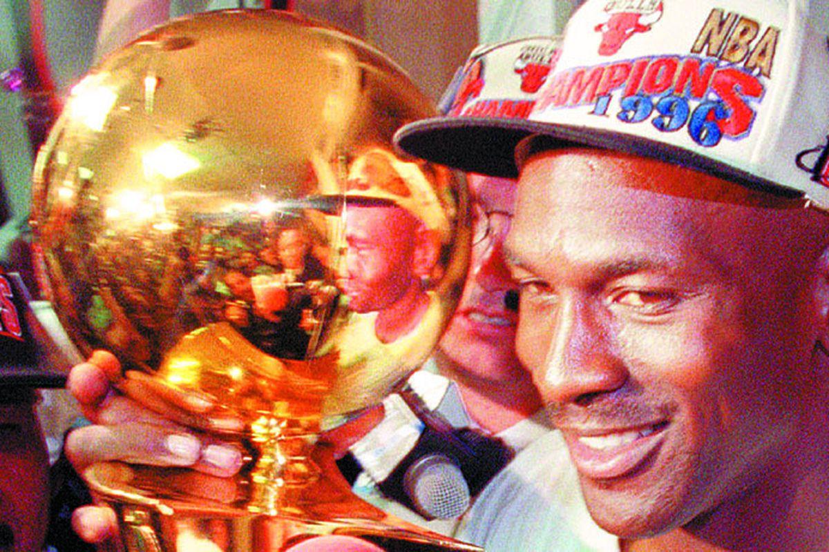Michael Jordan hold the Bulls' fourth NBA championship trophy.