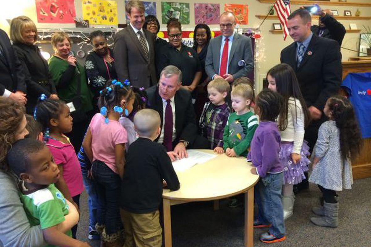 Mayor Greg Ballard signs the city's preschool ordinance in December at Warren Township Schools.