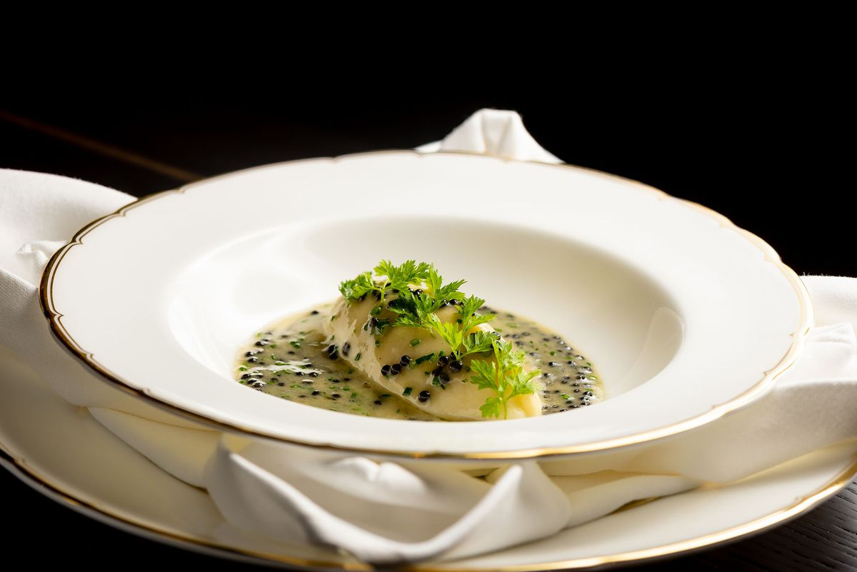 A quenelle of scallop with caviar in a refined bowl.