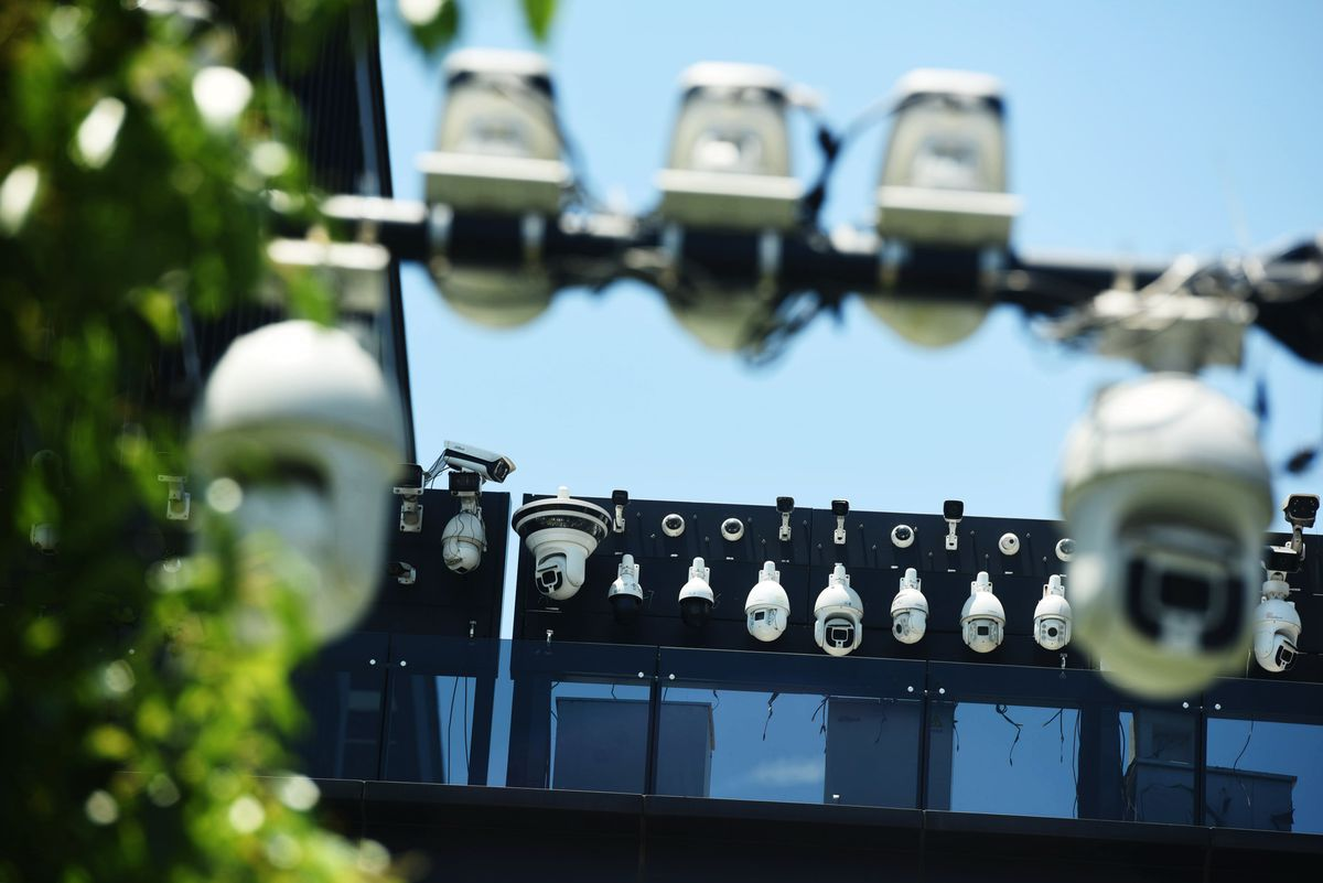 A thicket of security cameras positioned on top of a modern office building.