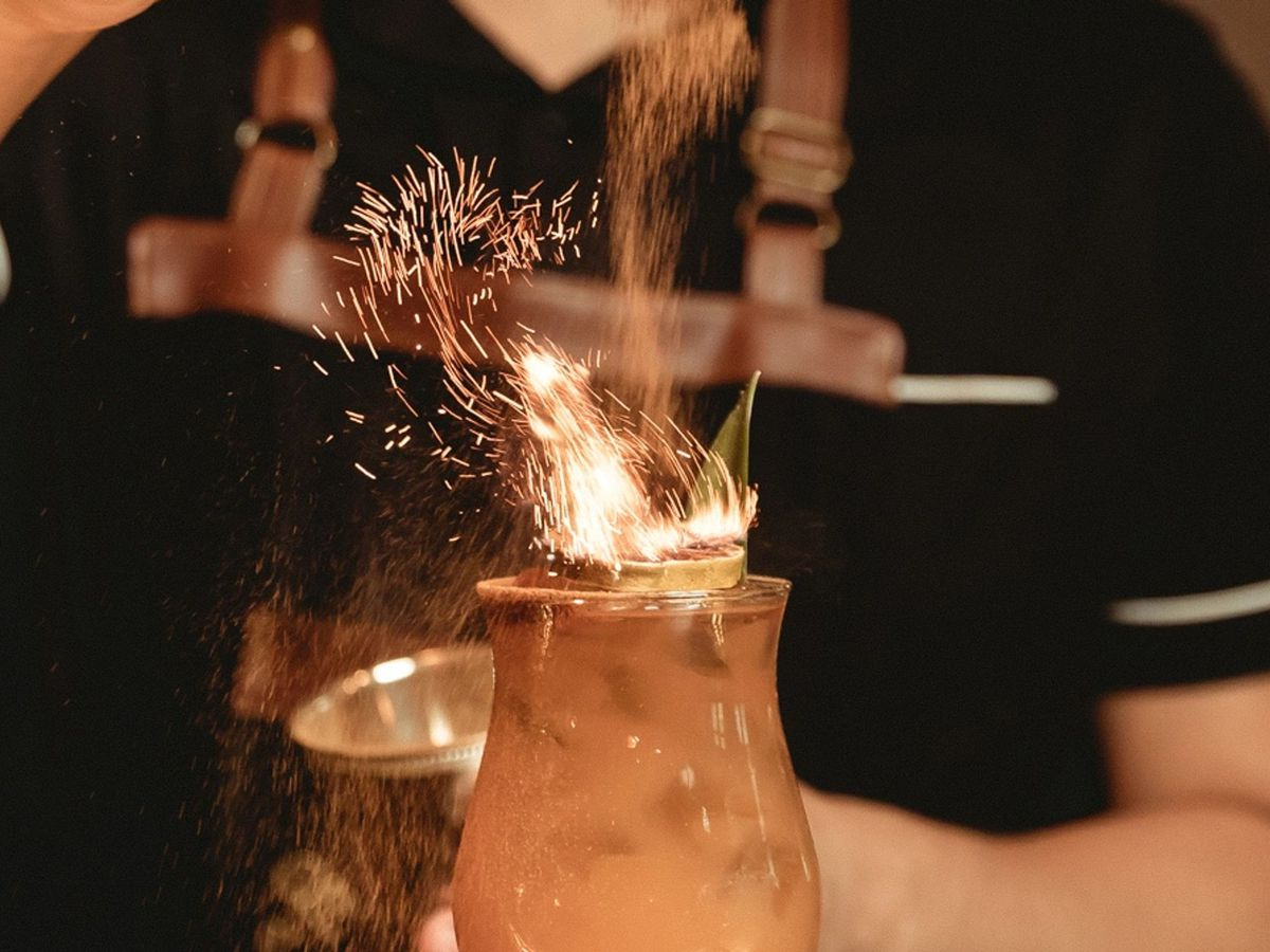 A bartender shakes a spice jar over a cocktail to make its flaming garnish flare up