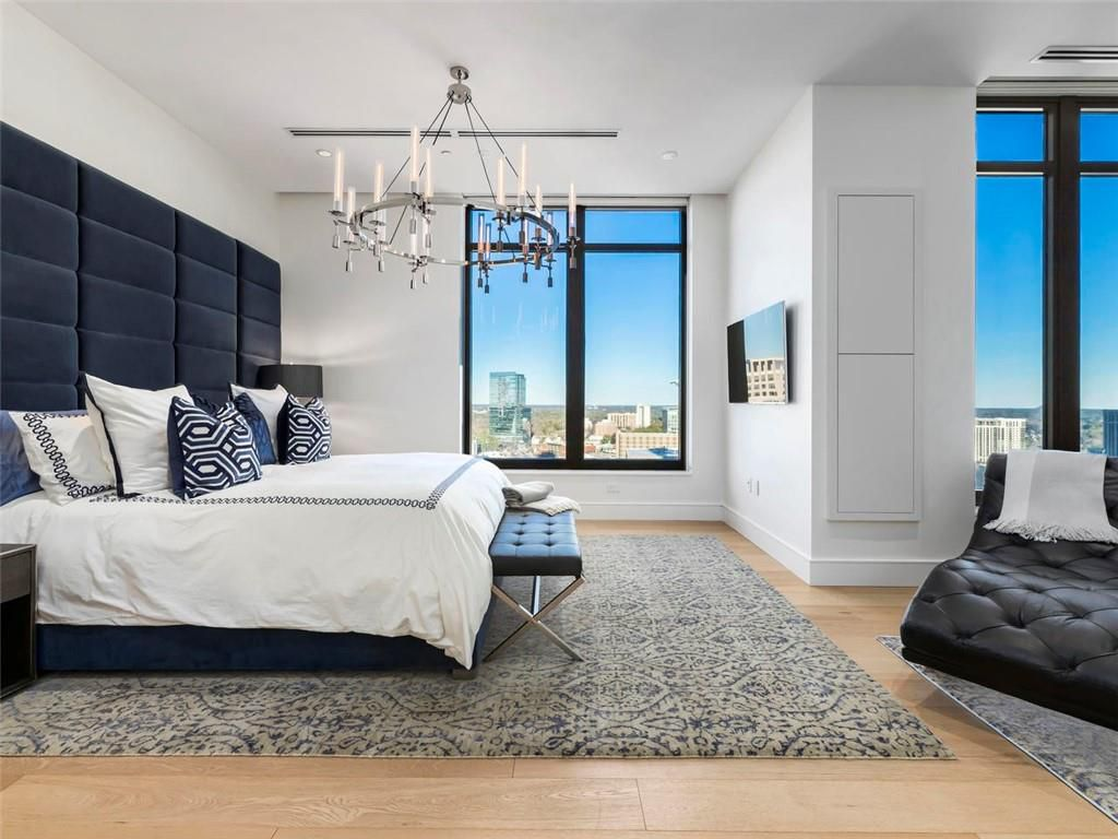 A blue and white master bedroom with a chandelier.