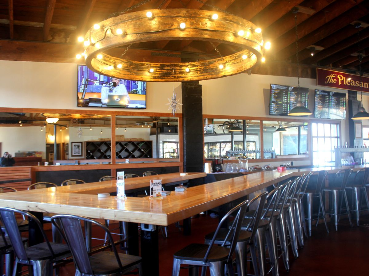 A row of counters and seats surround a halo-like lamp lighting the inside of Beer Star, with TVs on in the back.