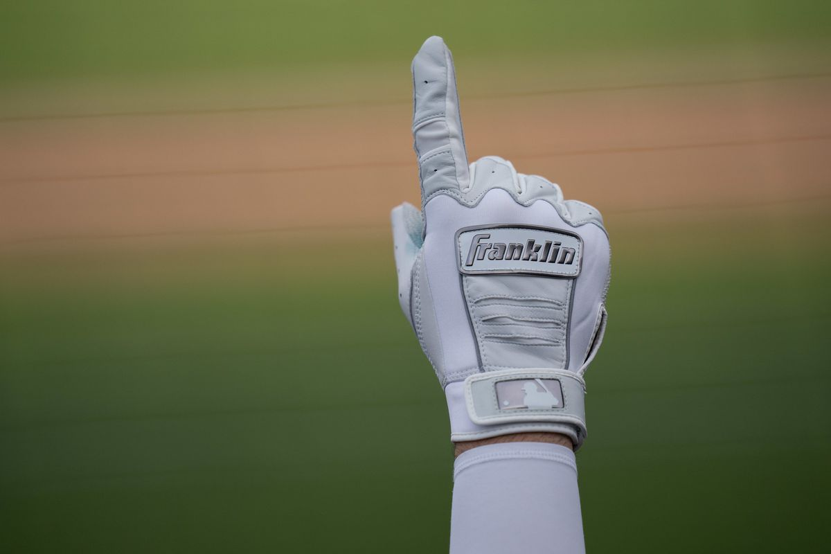 A hand clad in a white Franklin brand batting glove with silver accents points up in the air, and is the only thing visible against a distant backdrop of the green grass and brown dirt of a baseball diamond.