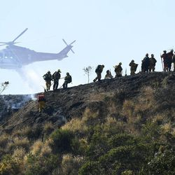 Camp crews pull a line up a hill while a slow moving grass and brush fire threatens homes in Burbank, Calif., Wednesday, June 28, 2017. Dozens of homes were under mandatory evacuation orders on the suburban edges of Burbank, where flames raced uphill through tinder-dry grass.