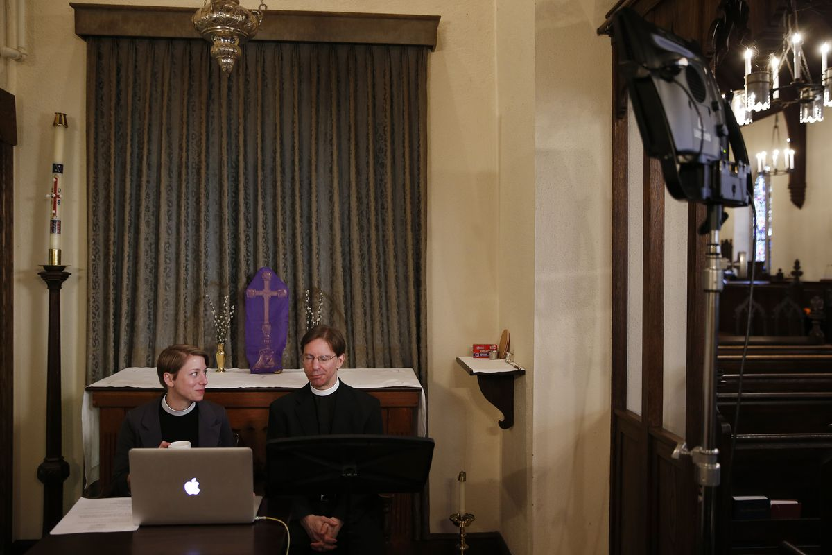 Two rectors look at a laptop in a church in Boston on March 15, 2020.