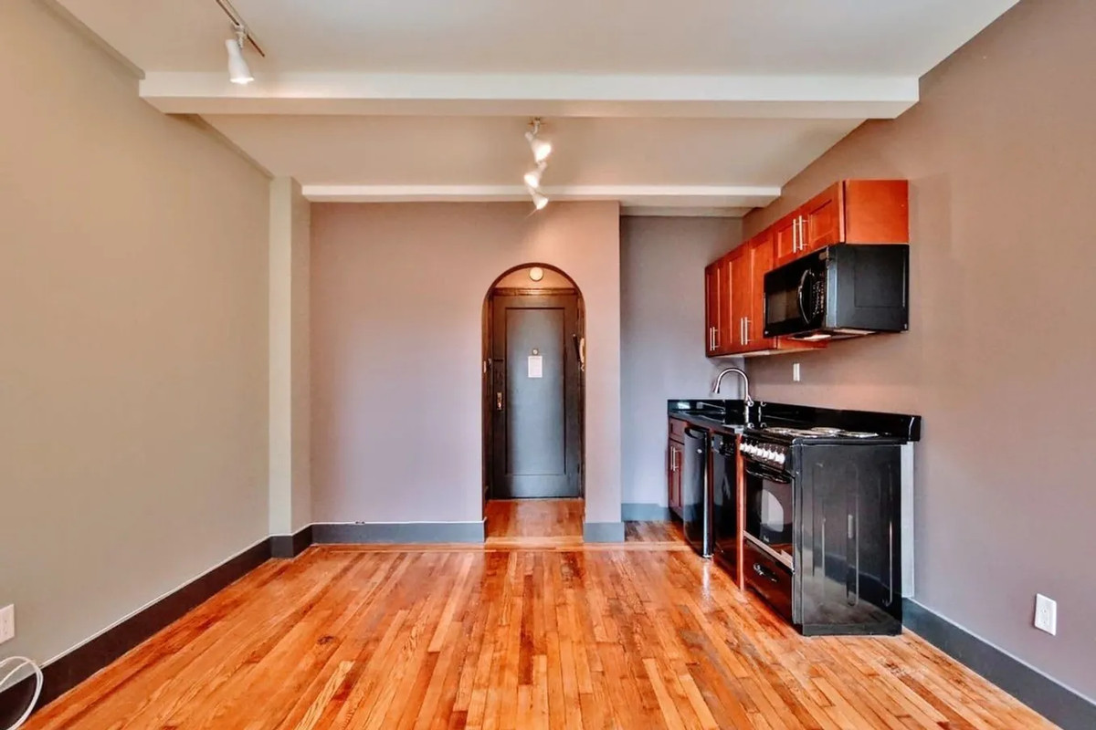 A living area with an arched entryway, hardwood floors, and a small open kitchen.