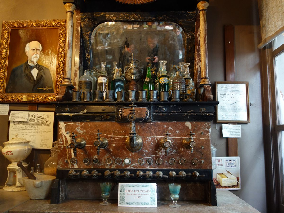 The interior of the New Orleans Pharmacy Museum. There are various objects and bottles on shelves.