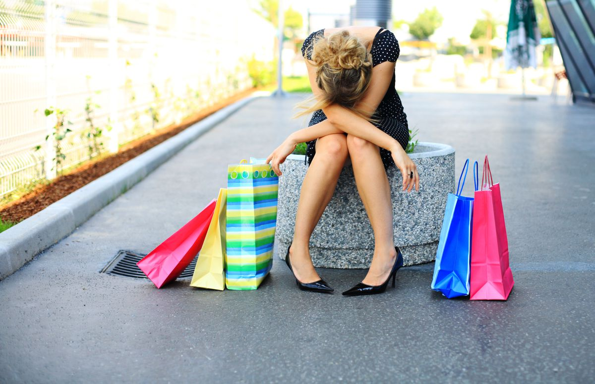 Woman with her head down surrounded by colorful shopping bags