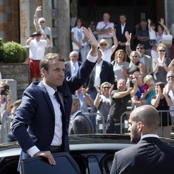 """French President Emmanuel Macron waves to the audience as he leaves a polling station in Le Touquet, northern France, after casting his vote in the first round of the two-stage legislative elections, Sunday, June 11, 2017. French voters are choosing legislators in the first round of parliamentary elections, with President Emmanuel Macron's party """"Republic on the Move"""" hoping to win a strong majority in the National Assembly to push through bold labor and security reforms."""