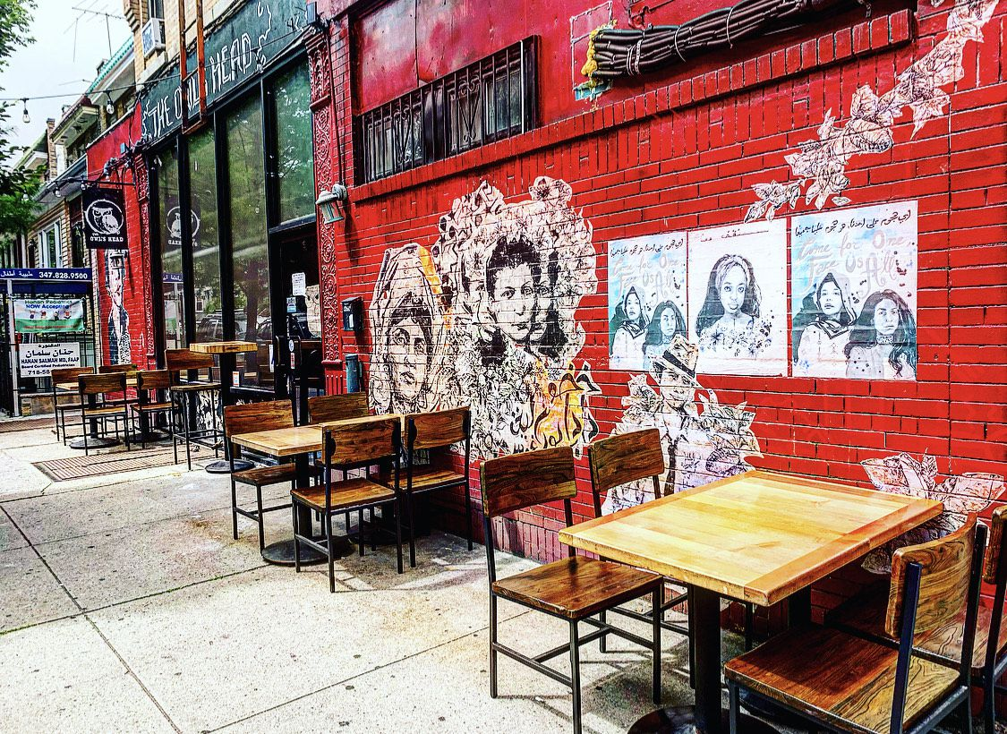 Wooden tables and chairs set up outside Bay Ridge bar the Owl's Head