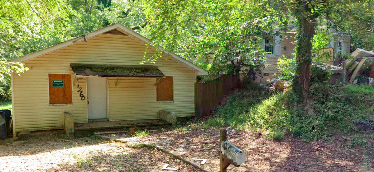 Two small rundown houses with trash in front yards.