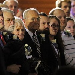 Patti Edwards, surrounded by family, stands as the casket is taken out at the memorial for former BYU football coach LaVell Edwards at the Provo Convention Center on Friday, Jan. 6, 2017.