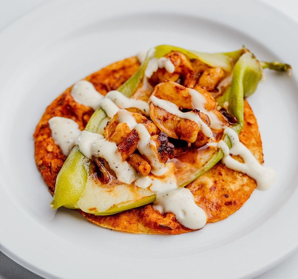 A pepper stuffed with shrimp and cheese on a tortilla drizzled with sauce on a white plate and neutral background