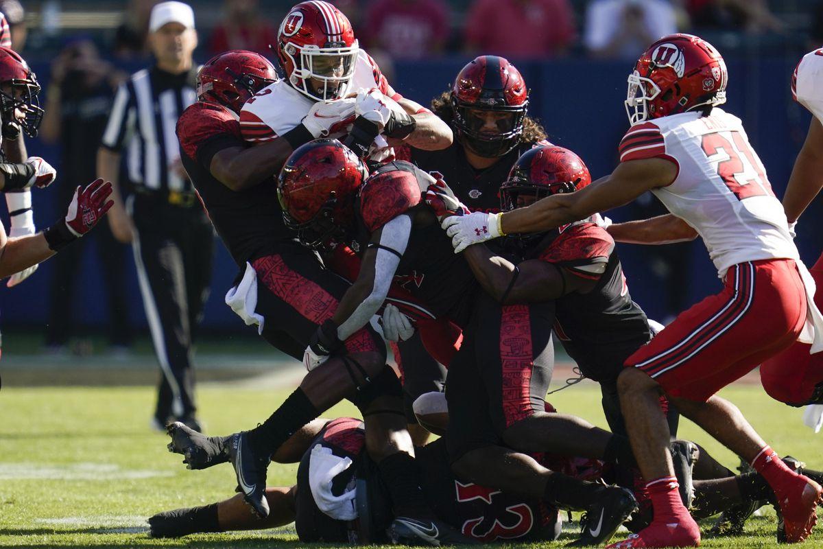 Utah running back Micah Bernard is tackled by San Diego State defenders.
