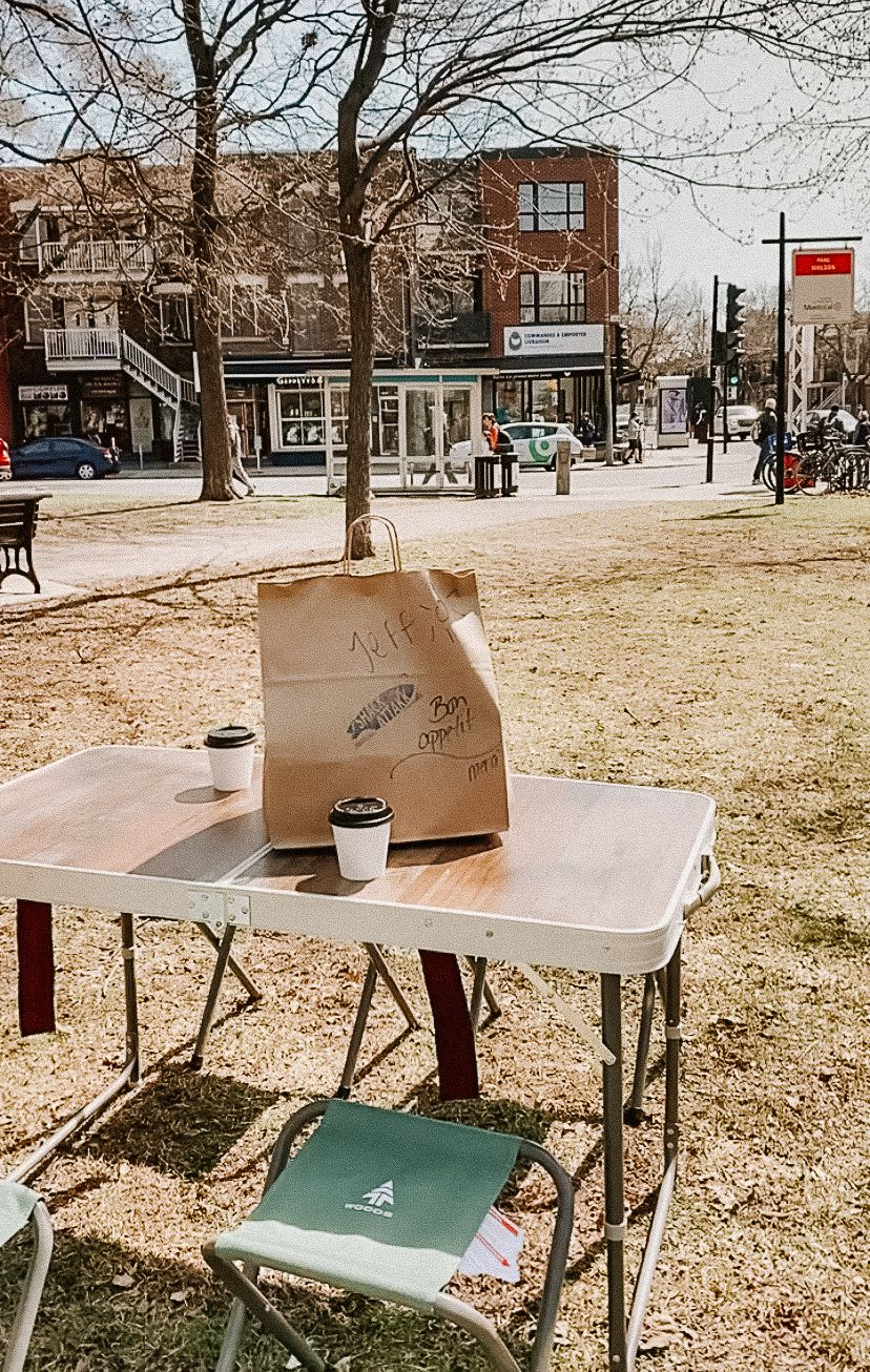 camping table with takeout bag and coffee cups on top