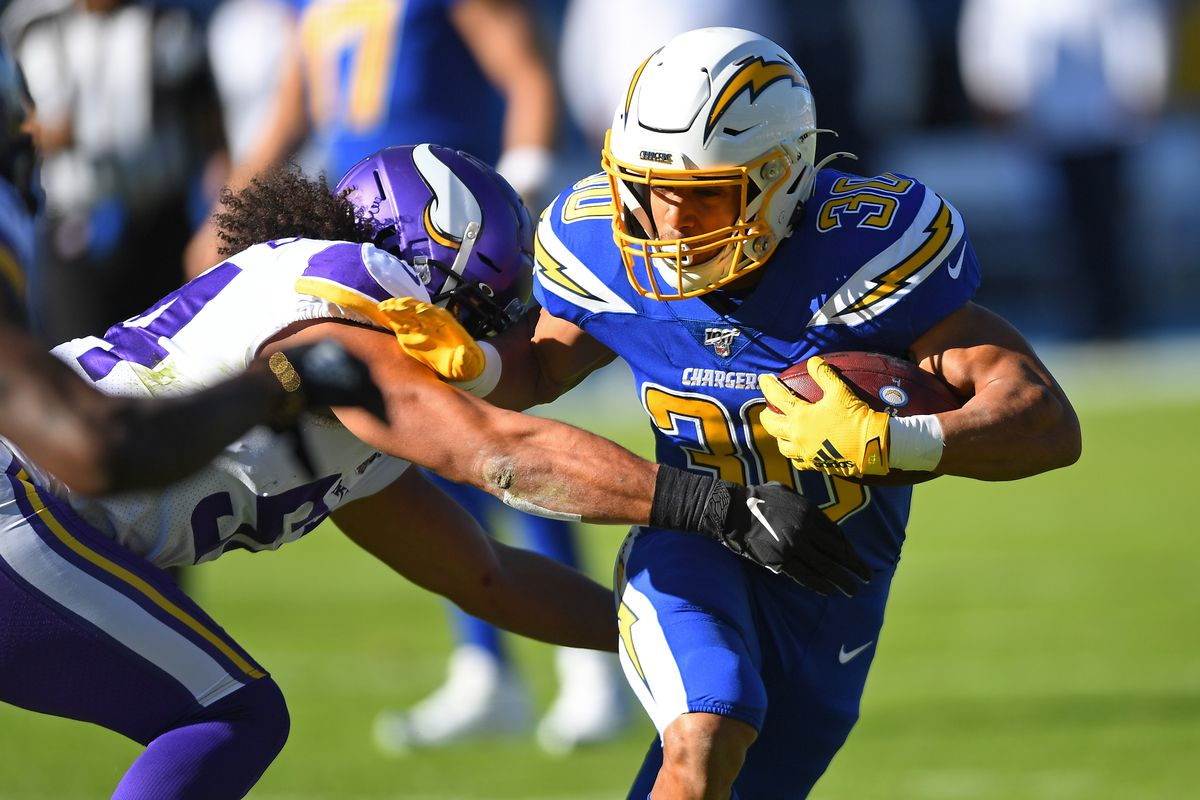 Running back Austin Ekeler #30 of the Los Angeles Chargers runs for a first down before he is stopped by middle linebacker Eric Kendricks #54 of the Minnesota Vikings in the first half at Dignity Health Sports Park on December 15, 2019 in Carson, California.