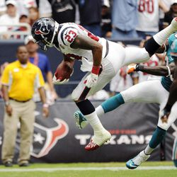 Houston Texans running back Arian Foster (23) leaps into the end zone for a touchdown as Miami Dolphins defensive back Chris Clemons, right, tries to tackle him in the second quarter of an NFL football game, Sunday, Sept. 9, 2012, in Houston.