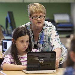 Substitute teacher Patrice Cullimore helps Lydia York in class Monday, March 30, 2015, at Endeavour Elementary in Kaysville.