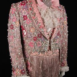 Fabergé suit: Perhaps the most ornate of Liberace's costumes, this pink gabardine and silk suit is covered with satin appliques, pastel seed and bugle beads, crystals, and pearls. He wore this jumpsuit and tailcoat in his Radio City Music Hall Easter show