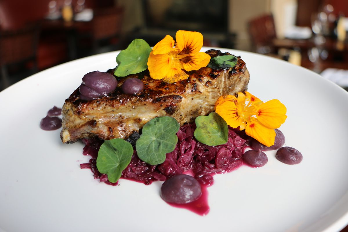 Closeup on a pork chop on a white plate, sitting on a vivid pile of purple cabbage and garnished with yellow flowers, large green leaves, and dollops of purple sauce
