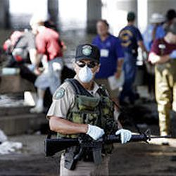 An armed officer, masked against the stench and possible contagion of fetid water, stands watch over an evacuation point in New Orleans on Wednesday.