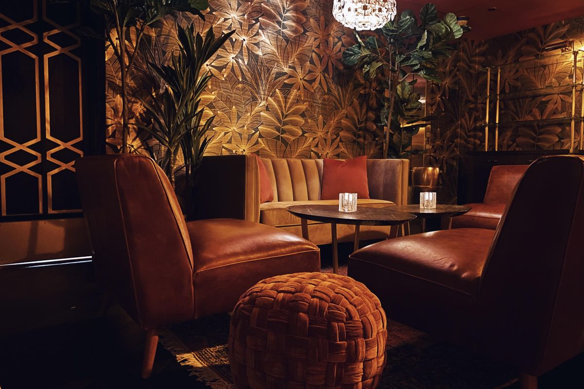 A corner booth in a dim, intimate bar with brown leather sofas and gold plant-patterned wallpaper.