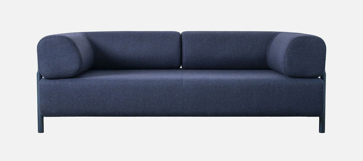 A minimalist navy blue sofa with curved back cushions.