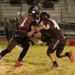 Jaren Hall (1) with a hand off for Maple Mountain.