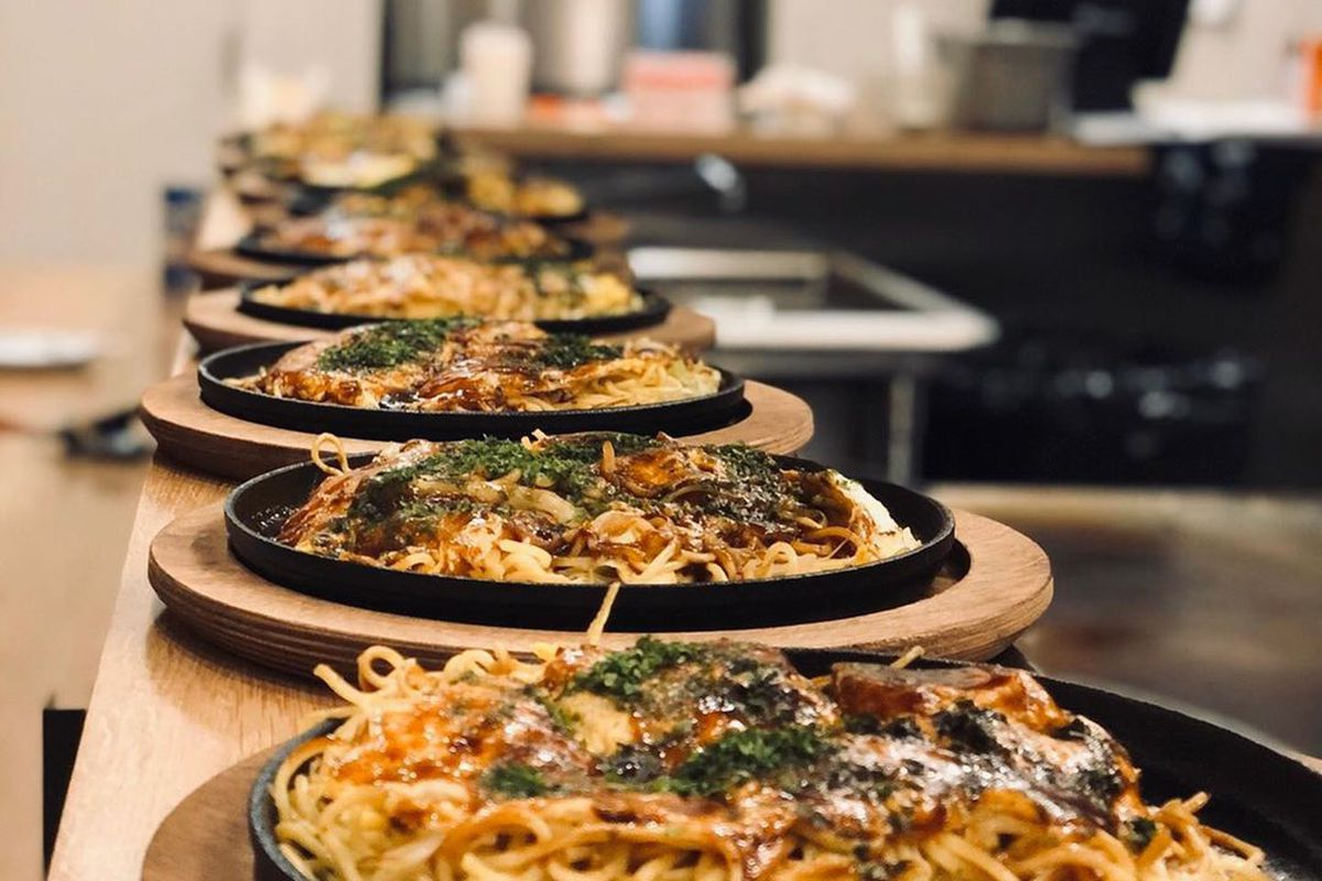 A line of cast iron dishes sitting on wooden trays are lined up on a restaurant counter, They each hold a Japanese noodle dish.