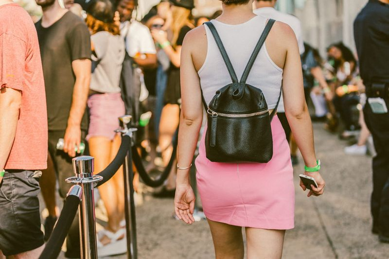 A woman walking through a crowd wearing a white shirt, pink skirt, and black backpack.