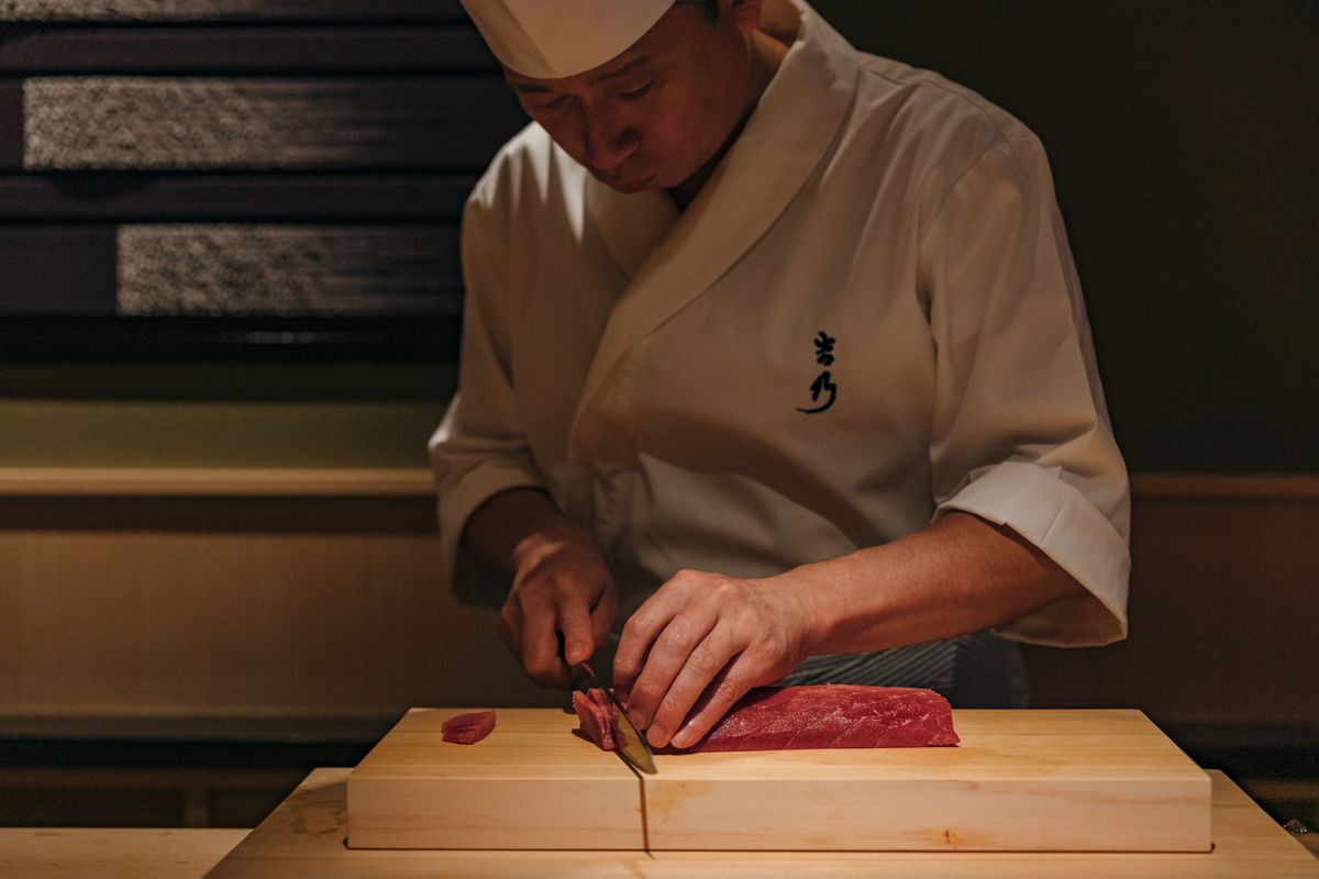 A chef in a white uniform slices raw red tuna on a wooden cutting board.